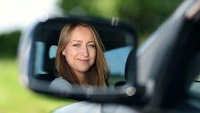 Водитель молодой женщины смотря зеркало взгляда со стороны автомобиля