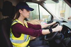 Водитель поставки управляя фургоном с пакетами на месте Стоковая Фотография