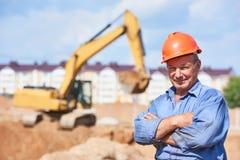 Водитель рабочий-строителя перед затяжелителем экскаватора Стоковое Изображение