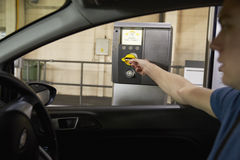 Водитель собирает билет от машины в автостоянке стоковые изображения