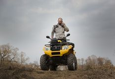 Водитель ATV говоря на телефоне пока управляющ Стоковое Изображение