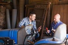2 водителя работая с трактором Стоковое Фото