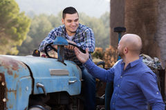 2 водителя работая с трактором Стоковое Изображение