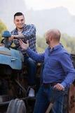 2 водителя работая с трактором Стоковые Изображения