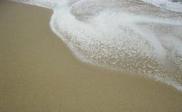 Волна бежать над песком стоковое изображение
