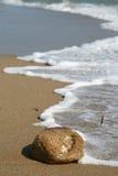 Волна и камень на пляже Стоковое Изображение RF