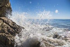 Волна разбивая против утеса Стоковые Изображения