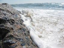 Волна ударяя утес Стоковые Изображения