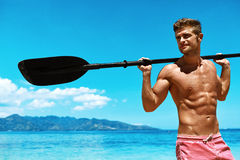 Водные виды спорта лета Человек с затвором каяка каное на пляже Стоковые Изображения