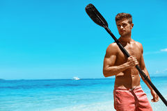 Водные виды спорта лета Человек с затвором каяка каное на пляже Стоковая Фотография RF