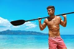 Водные виды спорта лета Человек с затвором каяка каное на пляже Стоковые Фото