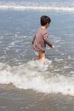 Волны мальчика входя в Стоковые Фото