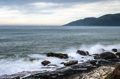 Волны моря воды брызгая на утесах моря Стоковое Изображение
