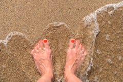 Волны моря океана и ноги девушки на песчаном пляже Стоковые Изображения RF