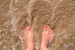 Волны моря океана и ноги девушки на песчаном пляже Стоковое фото RF