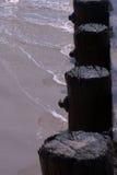 Волны моя вверх против деревянных штабелевок пляжа Стоковые Изображения