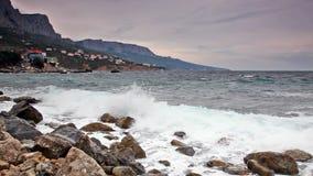 Волны ломают с брызгают о больших камнях на восходе солнца сток-видео