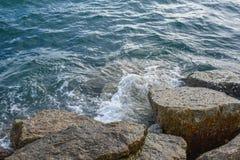Волны ломая на береге с морем пенятся Стоковые Изображения