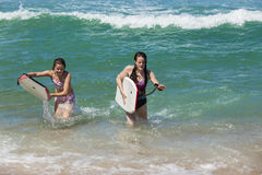 Волны пляжа доск девушек стоковое изображение