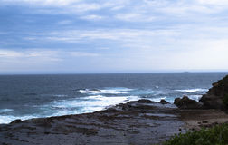Волны свернутые на берег и ломающ на утесах стоковое фото