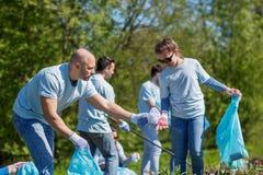 Волонтеры при сумки отброса очищая район парка стоковая фотография