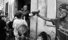 Волонтеры распределяя основной пищевой продукт к бездомным и необходимым людям