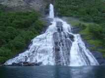 Водопад вызвал вздыхателя пропуская в фьорд Geiranger, Норвегию Стоковое фото RF