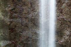 Водопад выдержки затвора холодного потока свежей воды длинной запачкал движение на темных каменных утесах в парке Стоковое Фото