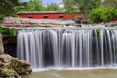 Водопад и красный крытый мост Стоковая Фотография
