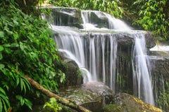 Водопад и утесы покрытые с мхом Стоковая Фотография