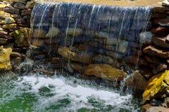 Водопад на фонтане источника малом в середине малого искусственного озера Стоковые Изображения