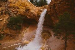 Водопад среди красных утесов и деревьев Стоковое фото RF