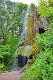 Водопад с пещерой среди зеленого сада Стоковые Изображения