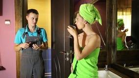 Водопроводчик имея flirt с маленькой девочкой дома люди с молодым женским клиентом перед flirt девушка нося полотенце ванны видеоматериал