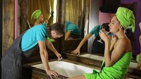 Водопроводчик имея flirt с маленькой девочкой дома люди с молодым женским клиентом перед flirt девушка нося полотенце ванны акции видеоматериалы