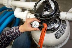 Водопроводчик проверяя манометр на большом гидронасосе стоковое изображение