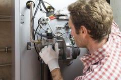 Водопроводчик ремонтируя конденсируя боилер в котельной стоковые изображения