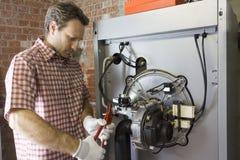Водопроводчик ремонтируя конденсируя боилер в котельной стоковая фотография