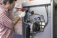 Водопроводчик ремонтируя конденсируя боилер в котельной стоковое изображение