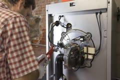 Водопроводчик ремонтируя конденсируя боилер стоковое изображение