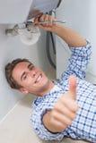 Водопроводчик ремонтируя сток washbasin пока показывающ жестами большие пальцы руки вверх Стоковые Изображения RF