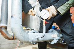 Водопроводчик устанавливая манометр на трубу стоковое изображение