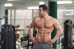 Волосатый мышечный человек изгибая мышцы в спортзале Стоковое Фото