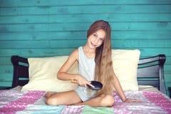 Волосы девушки чистя щеткой в спальне Стоковое Фото