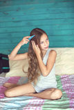 Волосы девушки чистя щеткой в спальне Стоковые Изображения