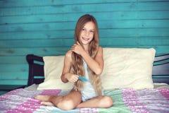 Волосы девушки чистя щеткой в спальне Стоковые Изображения RF