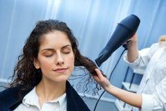 Волосы женщины засыхания стилизатора в салоне стоковое изображение