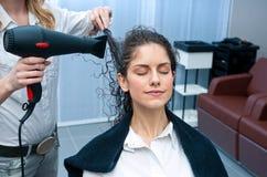 Волосы женщины засыхания стилизатора в салоне стоковые фотографии rf