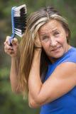 Волосы женщины чистя щеткой с пылевоздушным handbrush Стоковые Фото
