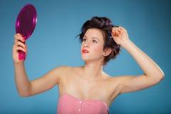 Волосы дизайна девушки при curlers смотря в зеркале Стоковое Фото